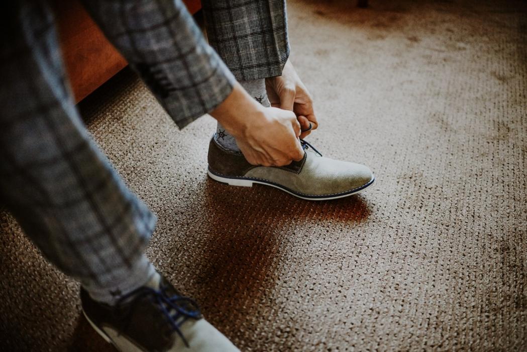Pan młody zakłada buty ślubne, retro ślub